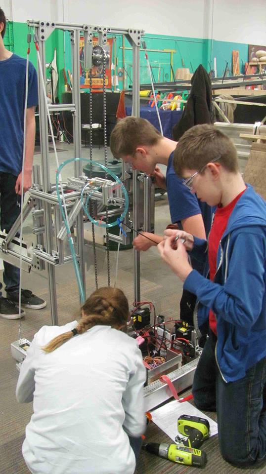 kids up close working on the robot